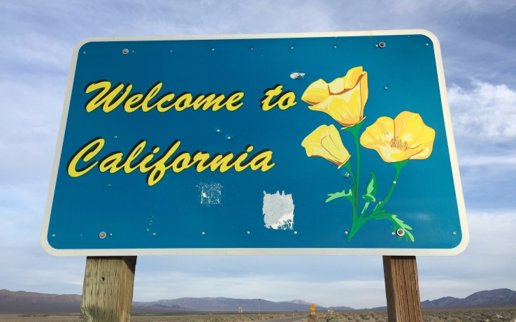 A blue road sign that says Welcome to California in script, alongside a picture of a California Golden Poppy. Behind the sign is a highway, leading to mountains and a cloudy, but bright horizon.